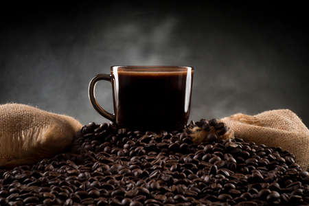 A cup of coffee on coffee beans with fragments of jute