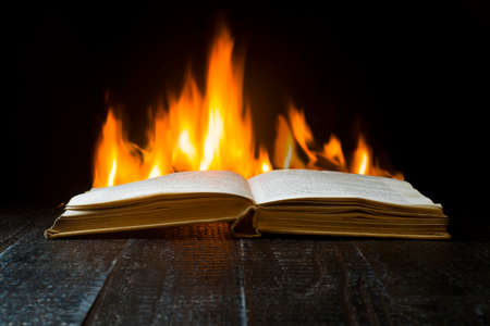 An open hardback book with flames in the background