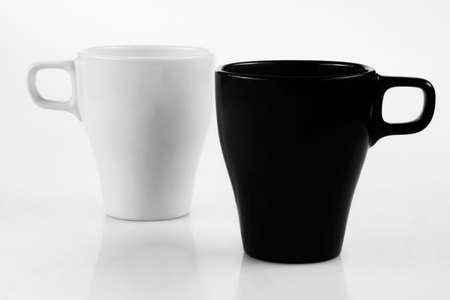 White cup and black mug isolated on a white background
