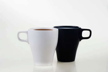 White cup with coffee and black cup with milk isolated on a white background