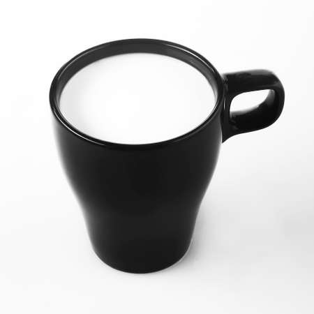 Black cup with milk isolated on a white background