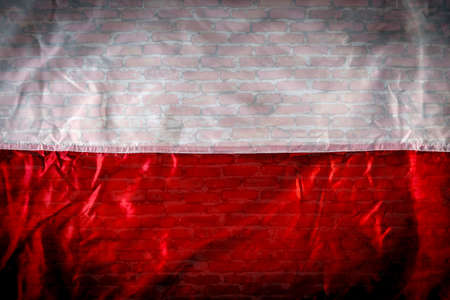 White-red flag on the background of a brick wall Фото со стока