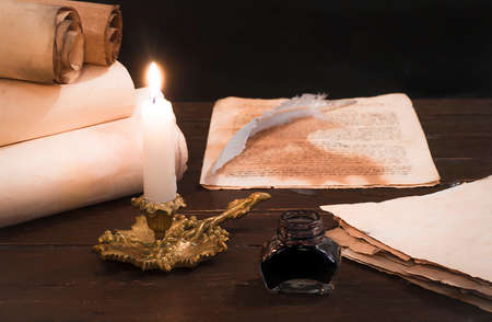 A lit candle on a background of blurred scrolls of parchment and bird feathers Stock Photo