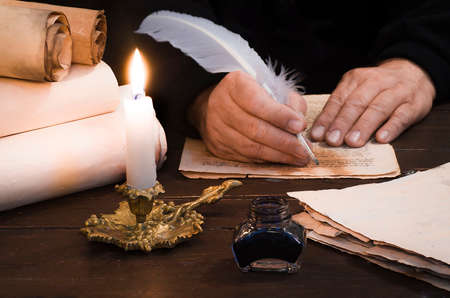 A lighted candle against the background of blurred scrolls of parchment, books and bird's feather