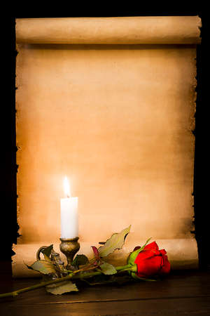 A scroll of old parchment, a red rose and a lit candle