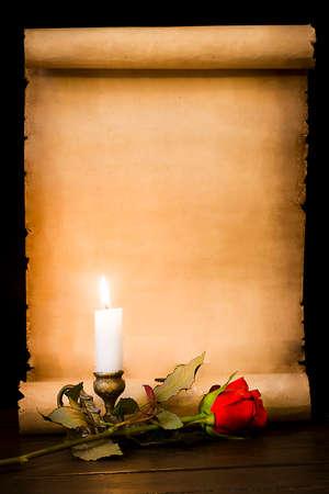 Un rouleau de vieux parchemin, une rose rouge et une bougie allumée