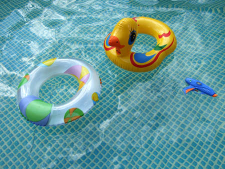 rubber ring: waterpool with toys and sky and clouds relfections in the water