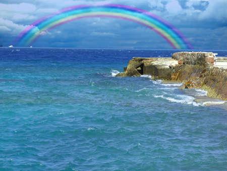 Rock op de zee, met mooie regenboog Stockfoto