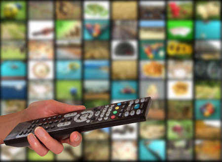 Remote in front of television screen Stock Photo