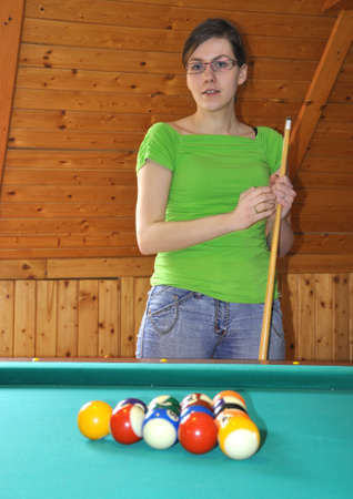 Young girl holding billard stick, ready to play a game photo