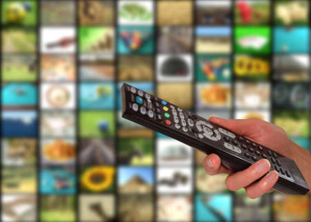 Remote in womens hand in front of multichannel background