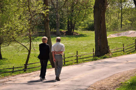 old people walking: Senior couple walking through the forrest
