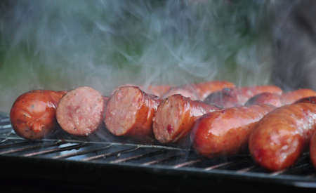 frankfurters: Sausages on grill, with smoke above it