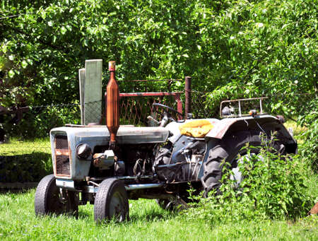 Old dirty tractor in bushes photo