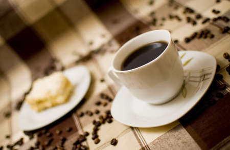 Coffee cup and cake on table, cake in blurred background photo