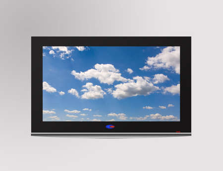 Modern flat television set with cloudscape on screen,  over a gray wall photo
