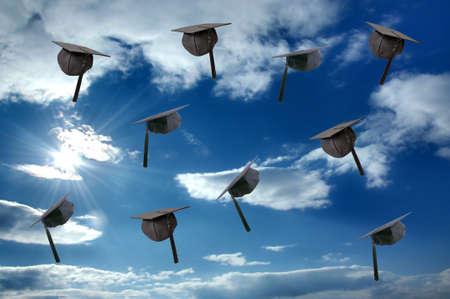 graduacion de universidad: Sombrero de graduación de estudiantes sobre cielo soleado