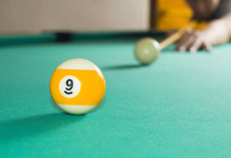 Billiard balls and man plaing billiard raedy to hit ball number nine