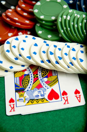 Casino gambling chips and playing cards on green poker background