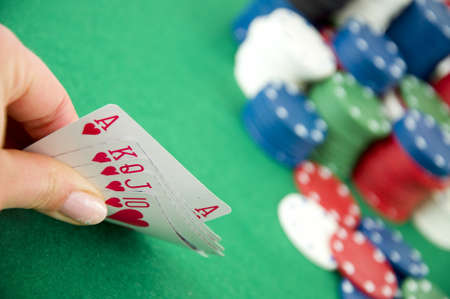 Casino gambling chips and playing cards on green poker background photo