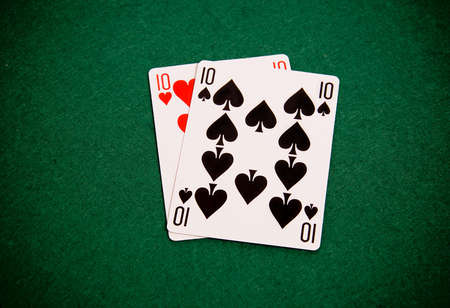 Playing cards on green background, pair of tens Stock Photo - 8821213