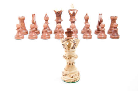 Alone against everyone, chess King against opposite army on white background photo
