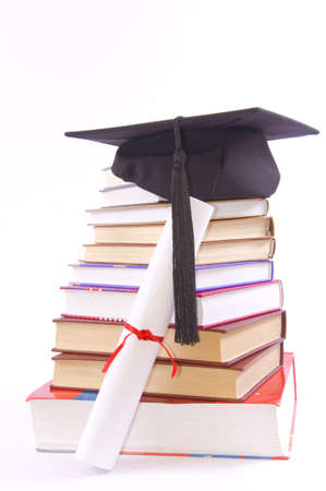Student hat on a tower made of books, against a white background - Education concept Foto de archivo