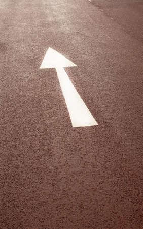 Straight arrow on the asphalt road photo