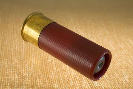 slug in a 12 gauge shotshell on a bright yellow and brown background Reklamní fotografie