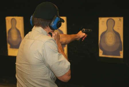 marksman practicing with a flashlight in a dark range