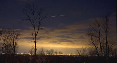 nightime: nightime Winchester Virginia in the winter with a single plane overhead