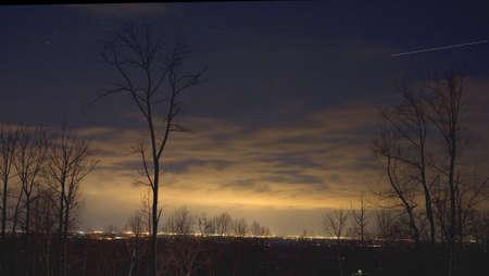 nighttime plane streaking across a starry sky photo