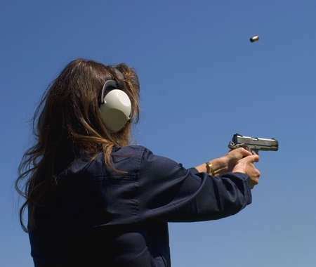female shooter practicing with a semi-auto pistol Stock Photo