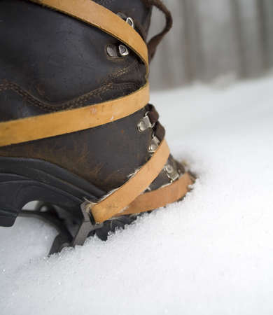 crampons: a boot with crampons thats in the snow