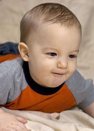 smirking: infant boy that is smirking as he crawls to something