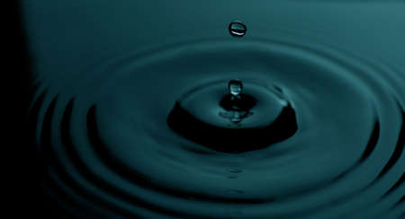 pair of water drops rising from the surface of more water Stock Photo