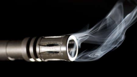 hider: barrel and flash hider on a gun that is smoking