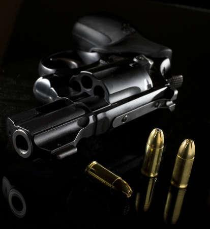 近くの弾薬とガラス テーブルの上は黒のリボルバー