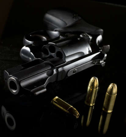 black revolver that is on a glass table with ammo nearby Stock Photo