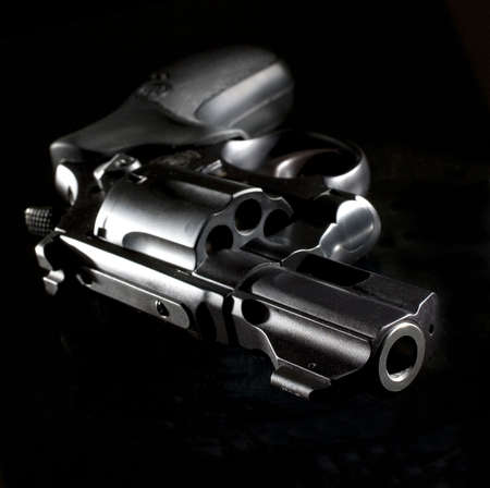 revolver that is starkly lit on a black background