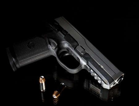 검은 유리 위에있는 총알이있는 권총 스톡 콘텐츠