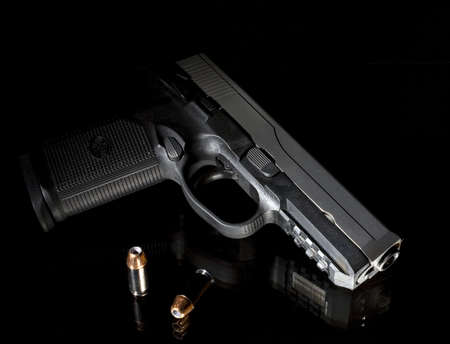 handgun with bullets that is on black glass