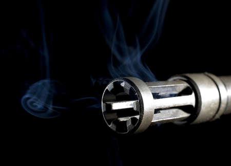 flash hider: apagallamas sobre un barril con humo de boca en el frente y el aumento de