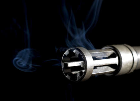 flash hider: muzzle hider on a barrel with smoke in front and rising