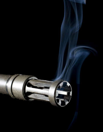 flash hider: barrel of a gun that is hot enough to be smoking Stock Photo
