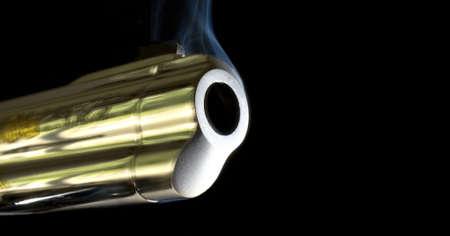 barrel of a pistol that is still smoking after a shot Фото со стока