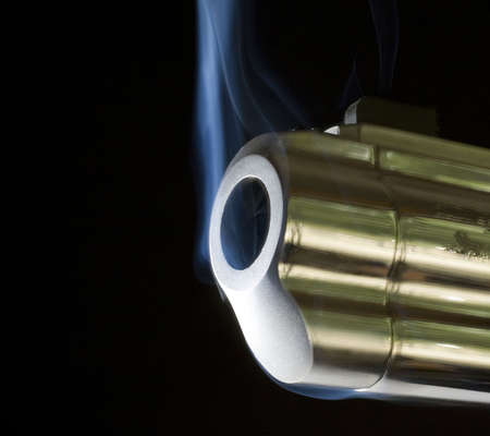 barrel of a revolver that is pouring out smoke