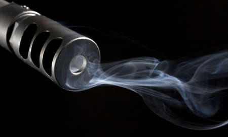 smoke that is pouring from the barrel of a sniper rifle