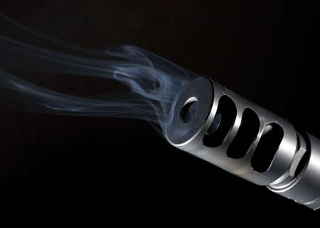 muzzle brake that is on a sniper rifle that is smoking