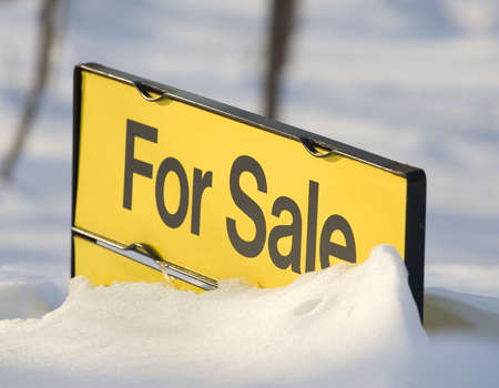house for sale sign that is buried in a deep snow